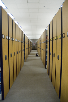 an aisle between rows of compact shelving