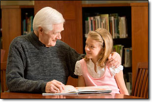 old man hugging young girl at table with book