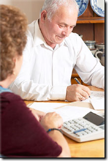 older man and woman at table with calculator and papers